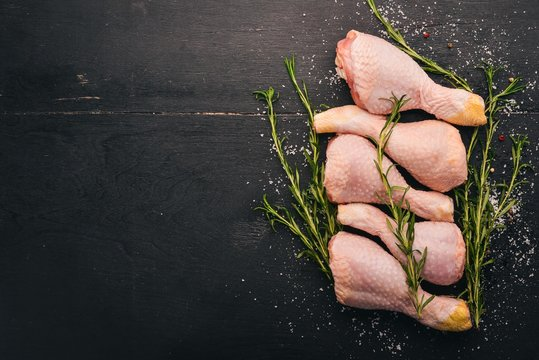 Raw chicken legs with rosemary and spices on a black wooden background. Top view. Free space for text.