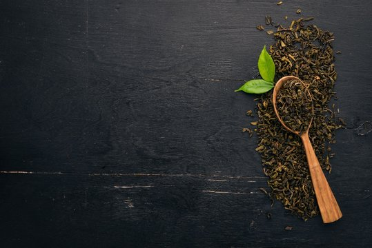 Dry green tea. On a wooden background. Top view. Copy space.