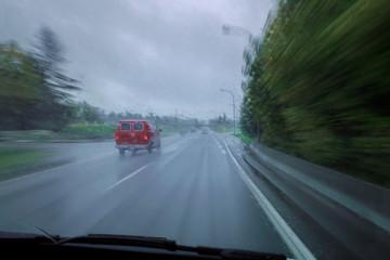 Roter Van auf verregneter Strasse aus dem verfolgenden Auto mit hoher Geschwindigkeit