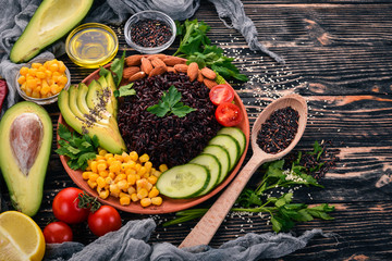 Black rice, avocado, cucumber, corn and almonds. On a wooden background. Top view. Free space for your text.