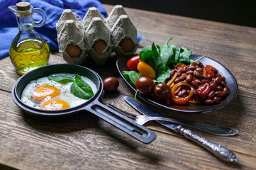 The pan fried eggs, haricot stewed in tomato sauce and fresh spinach. Concept of a healthy breakfast.