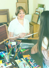Female artist painting portrait of woman