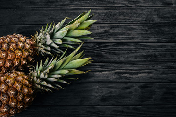Pineapple on a wooden background. Top view. Free space for text.