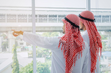back view of two young Arabian business man pointing and checking construction site in office building, successful, business, meeting, partner, teamwork, community, coworker and connection concept