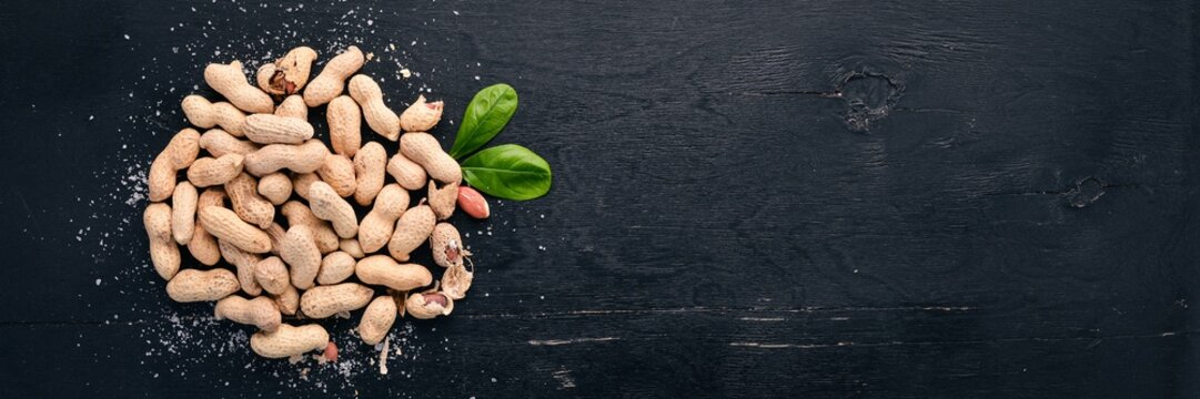 Peanuts on a dark wooden background. Healthy snacks. Top view. Free space for text.