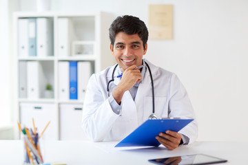 happy doctor with clipboard at clinic