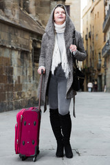 young girl in hood and coat with baggage