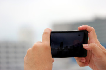 Human hands holding and touching a smartphone screen to take a photo.