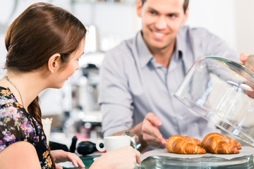 Friendly waiter offering to young female customer fresh French croissants for breakfast