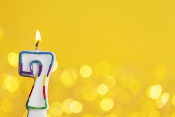Number 7 birthday celebration candle against a bright lights and yellow background
