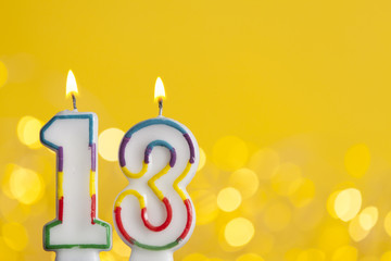 Number 13 birthday celebration candle against a bright lights and yellow background