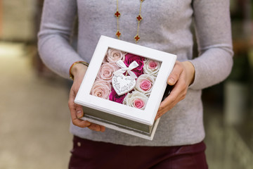 Box with flowers from white and purple roses in hands, background,Postcard, Valentine's Day, Women's Day, 8 march