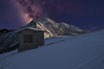 Milky Way above the snow-covered mountain with a small house in the foreground