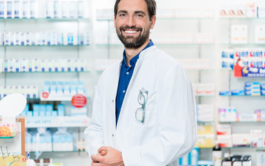 Apothecary in pharmacy store standing at shelf with drugs