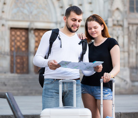 Cheerful man and woman traveling with map and baggage