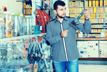 male customer examining various glue guns in store