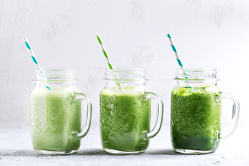 Variety of three color green spinach kale apple yogurt smoothie in mason jars in row with retro cocktail tubes over gray background. Healthy vegan detox eating.