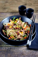 Rice noodles with fried beef, corn, green peas, red and green carrots, parsley and spicy sauce.