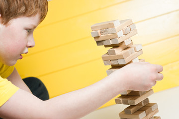 The child plays in board game falling tower of wooden blocks