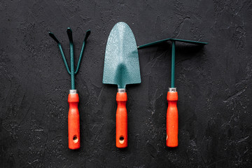 Gardening tools: spade, fork, hand cultivator, hoe on black background top view