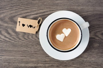 Cup of hot chocolate with heart shaped marshmallows and I love you tag over a wooden background