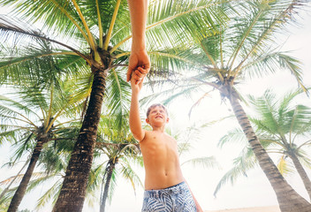 Happy smiling boy take for hand his father under palm trees