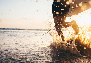 Man surfer run in ocean with surfboard. Closeup image water splashes and legs, sunset light