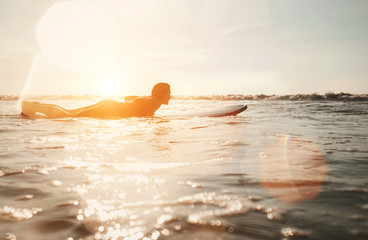 Woman surfer floating on the long surfboard towards line up