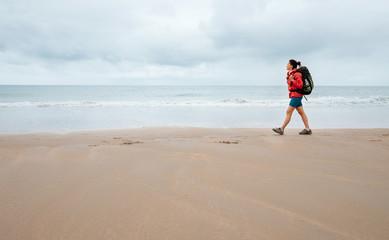 Woman traveler walk on empty ocean beach in rainy day