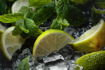 Lime slices with ice and mint on dark background.
