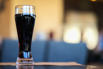 Glass of dark beer in bar or in pub close up. Real scene. Concept of beer culture, Craft brewery, uniqueness of beer grades, meeting of low alcohol beverage lovers