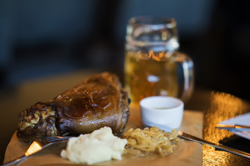 Pork shank with traditional side dish to beer. Blurred background. Real scene in bar, pub. Beer culture, uniqueness of beer grades, meeting of low alcohol beverage lovers. Selective focus