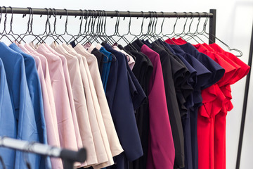 colorful women's dresses and other clothes on hangers in a retail shop. Fashion and shopping concept