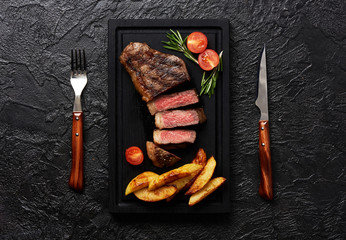 Meat Picanha steak, traditional Brazilian cut with tomatoes, potato wedges and rosemary on black meat cutting board. Steak with fork and knife. Black concrete background.