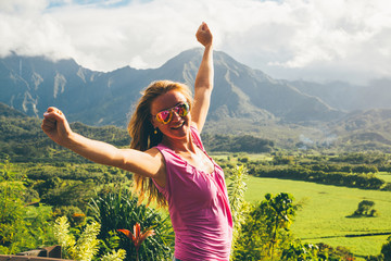 Beautiful sexy lady standing on the top of the peak with an amazing view on Kauai island in Hawaii watching landscape, mountains and green nature. Successful life. Living your life.