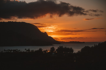Breathtaking sunset view over the Pacific ocean at the Kauai island, Hawaii with clouds and mountains. Retro style.