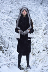 Woman with skating shoes in winter clothes in snowy forest