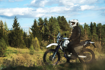 Biker man stands on the road forest and looks into the distance enduro