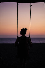Rear view of silhouette woman swinging at beach against sky during sunset