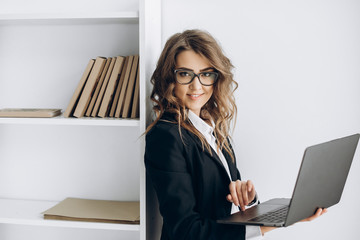Charming business woman with laptop in her hands at her office
