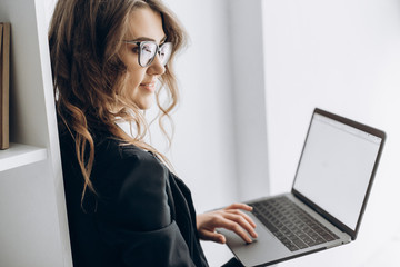 Attractive woman in a business suit and in glasses is holding a laptop in her hands