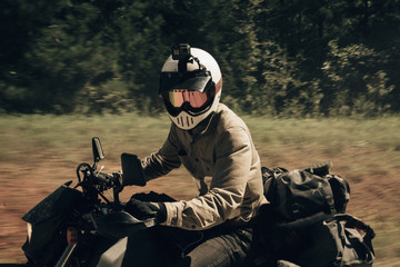 Side view of biker wearing crash helmet while riding motorcycle on dirt road