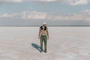 Shirtless young man standing at desert against sky
