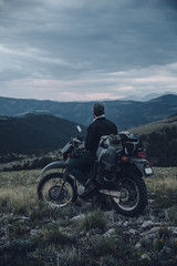 Rear view of biker sitting on motorbike against cloudy sky in forest during sunset