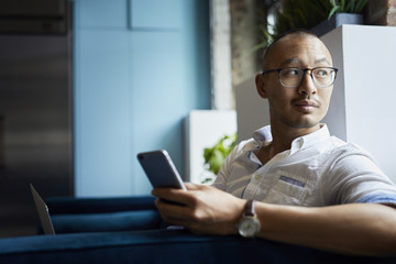 Businessman with mobile phone looking away while sitting on sofa at office