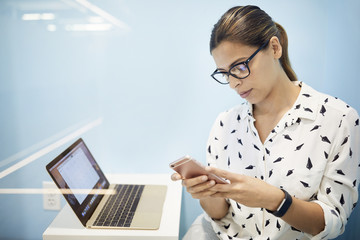 Businesswoman with laptop using smart phone in cubicle at office
