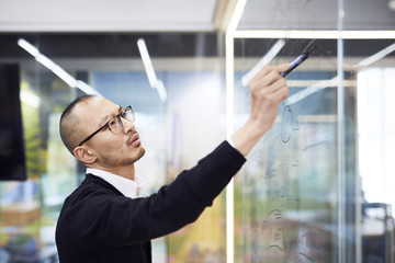 Business man writing on glass in office