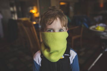 Portrait of boy with mouth covered by scarf at home