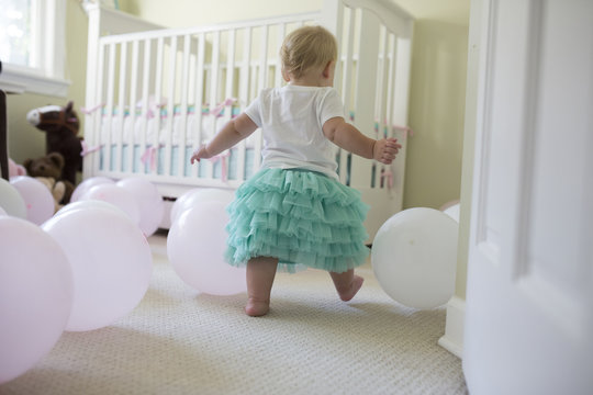 Rear view of baby girl playing with balloons at her birthday party