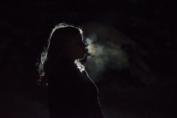 Side view of girl blowing smoke while standing in darkroom